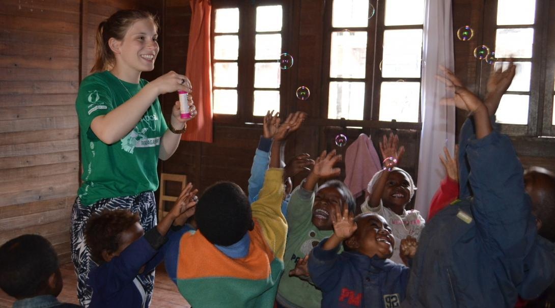 Projects Abroad volunteer with children in Madagascar blows bubbles for a group of children to catch at her Childcare placement.
